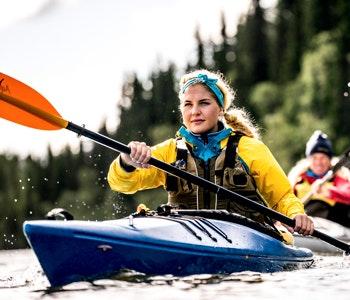 Tre paddlare på sjö i inland