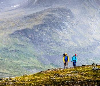 Vandrare på fjäll med berg i bakgrunden