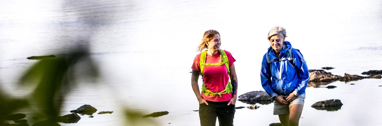 Två kvinnor vandrar vid sjö