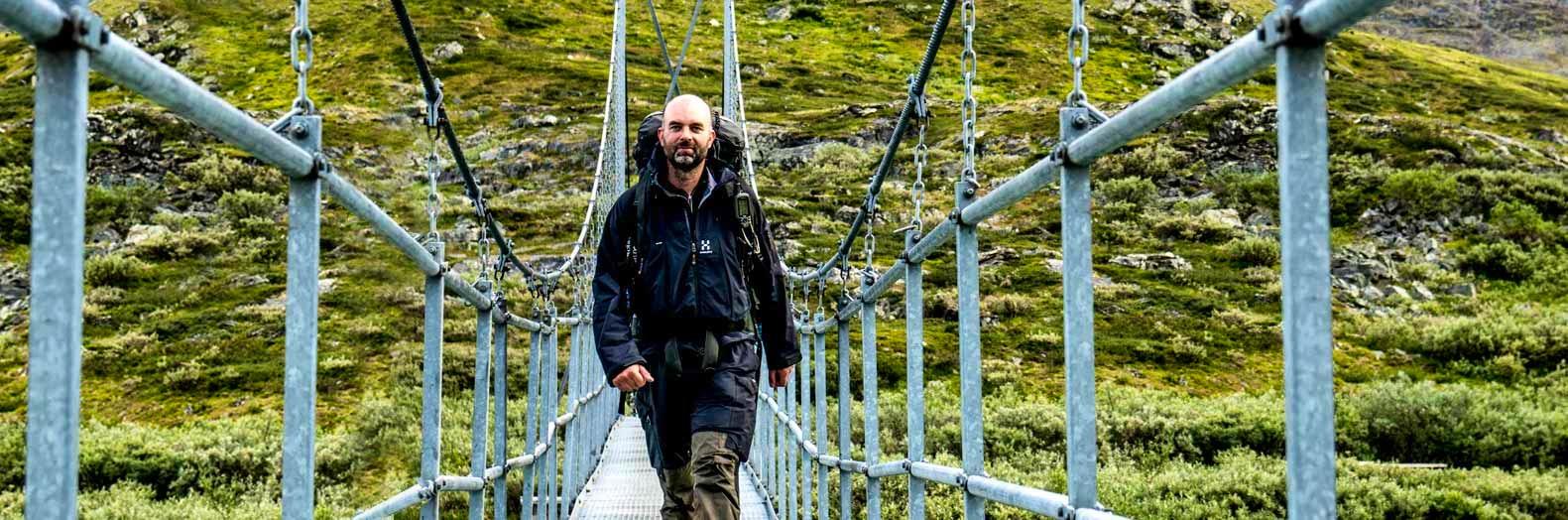 Manlig vandrare på hängbro på Kungsleden