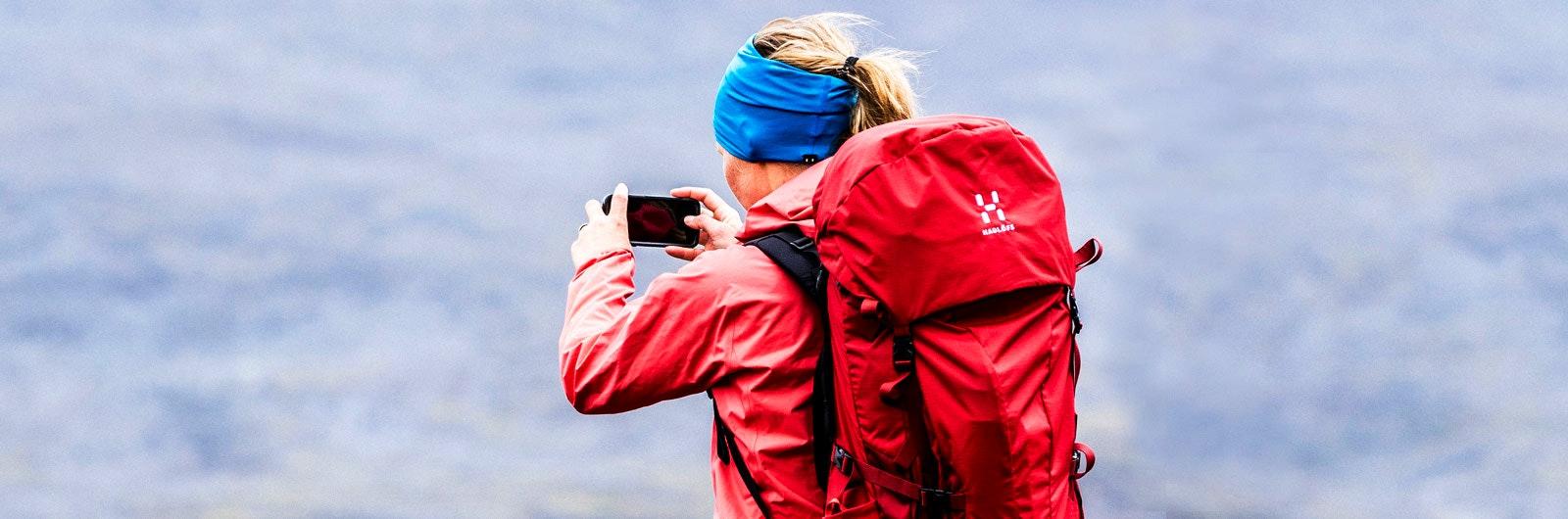 Rödklädd vandrare fotograferar landskapet