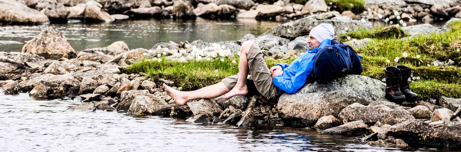 Man som vilar barfota vid vatten