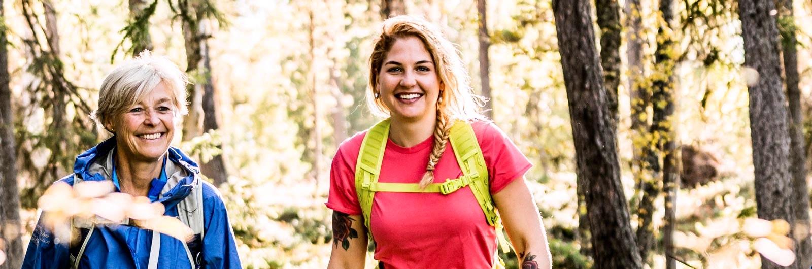 Två glada kvinnor på skogsvandring