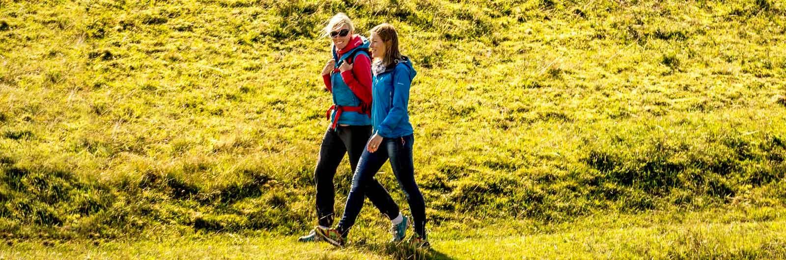 Två kvinnor vandrar på fält