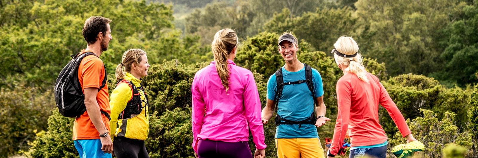 Fem löpare i färgglada kläder pratar