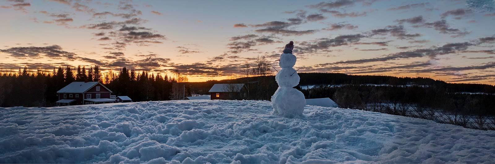 solnedgång på vintern vid stuga
