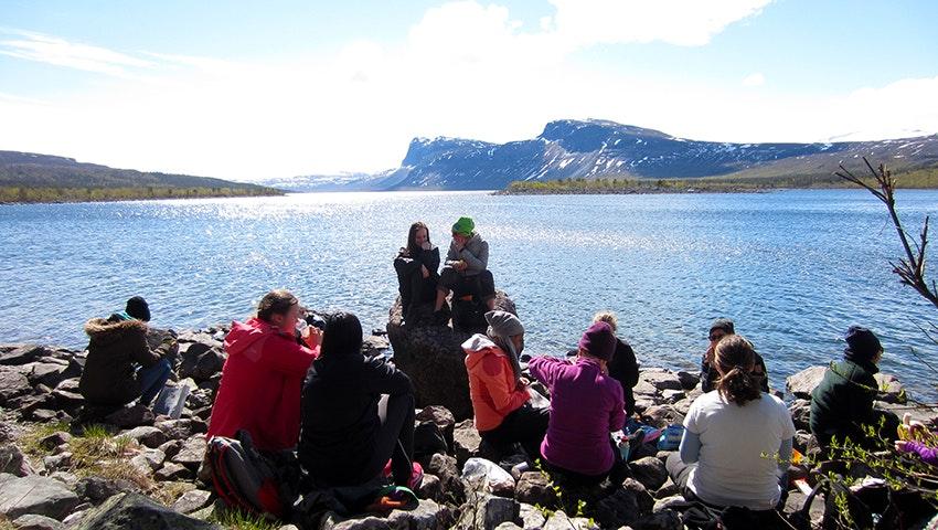 Ett tiotal tjejer har lunchpaus bredvid en fjällsjö
