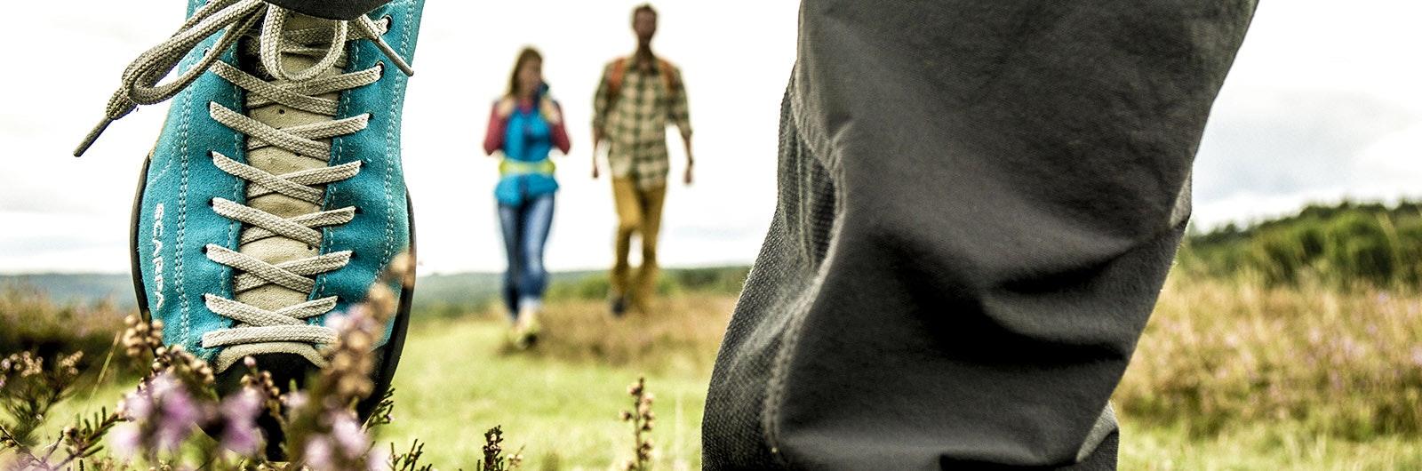 Närbild på ben med vandrare i bakgrund