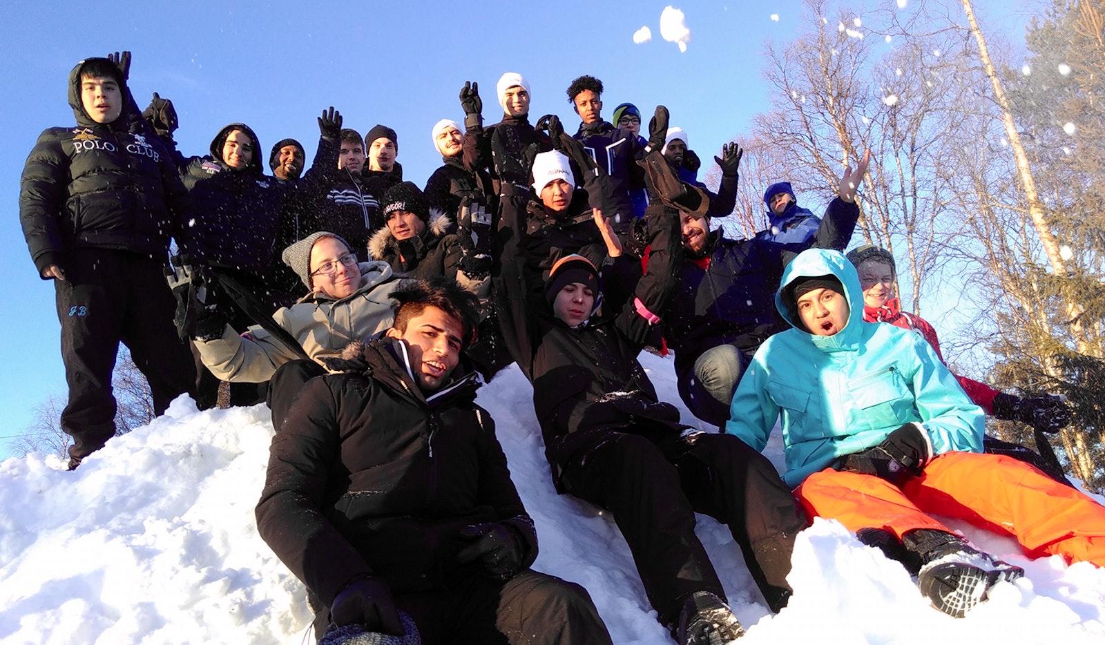 Stort gäng tonårskillar sitter på en snöhög