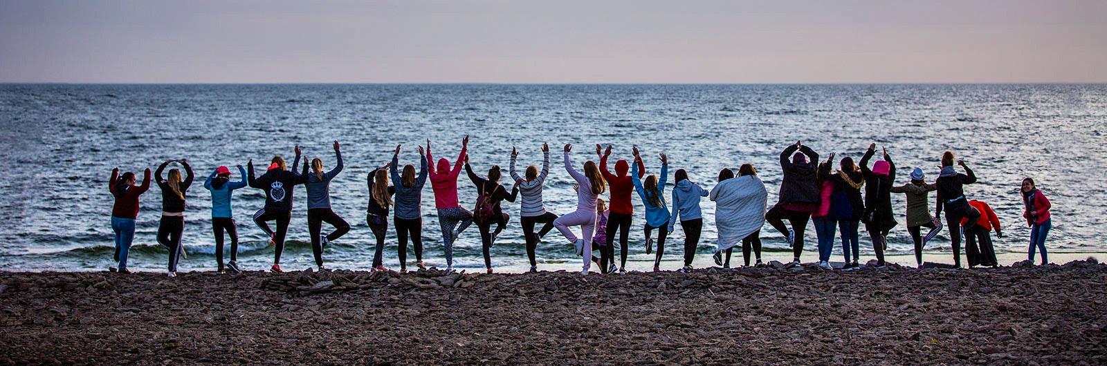 25 tonårstjejer står på rad i vattenbrynet vid havet