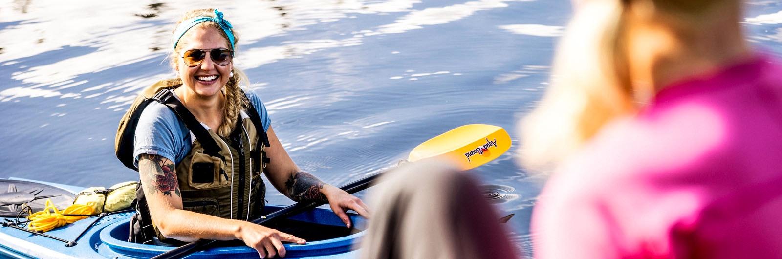 Kvinna som paddlar kajak
