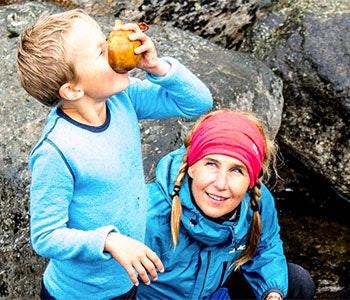 Barn som dricker vatten ur en fjällbäck