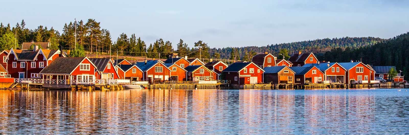 Röda små båthus vid Höga Kusten