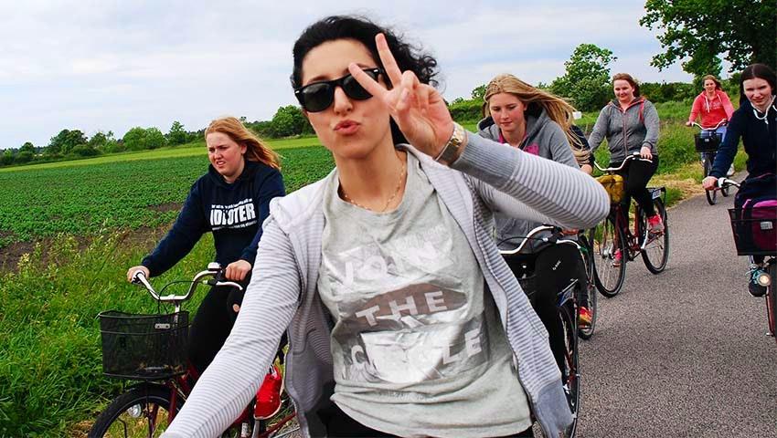 6 tonårstjejer cyklar tillsammans på en landsväg