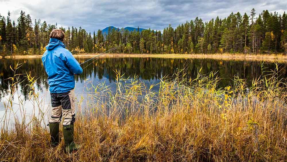 Fiskare i höstlandskap intill sjö