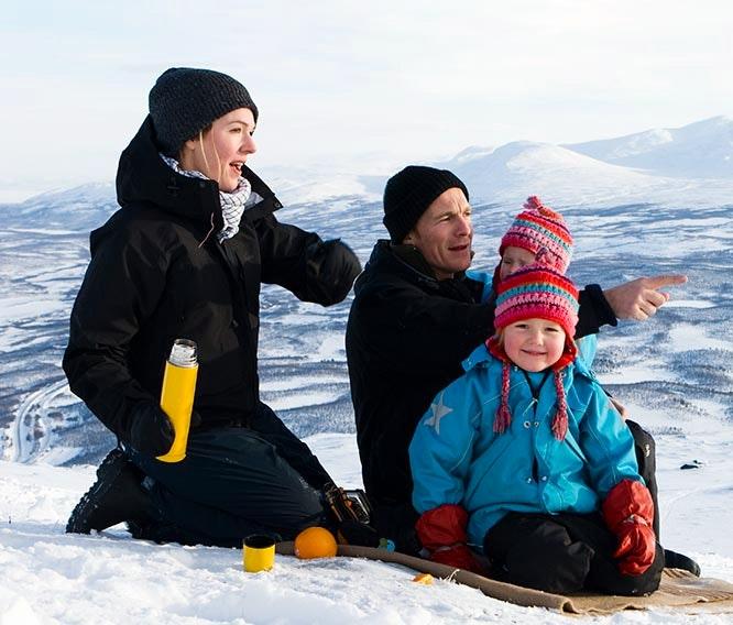 Barnfamilj äter fika i snön