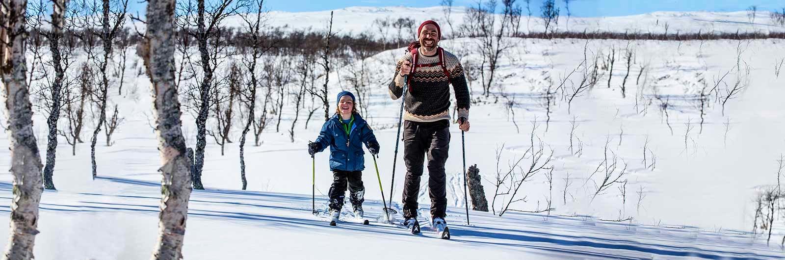 pappa och son som skidar på fjället