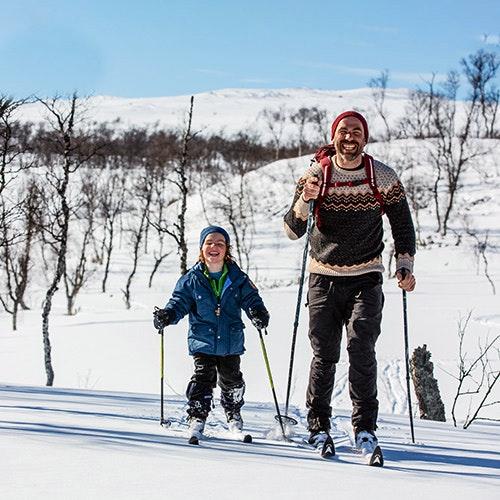 pappa och son åker skidor i fjällen