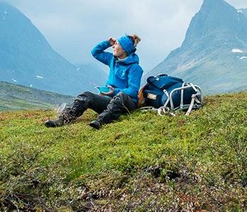 Fjällvandrare med blå jacka och ryggsäck vilar