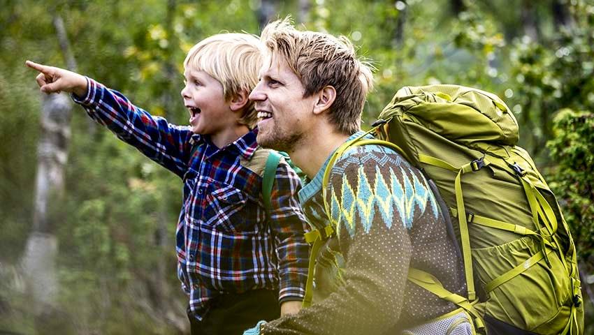 Pojke och pappa på upptäcktsfärd i skogen