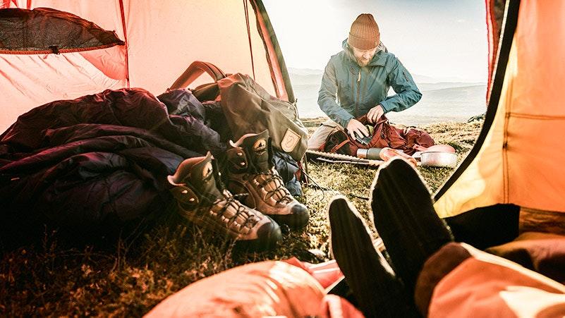 Kille packar ryggsäcken utanför tält
