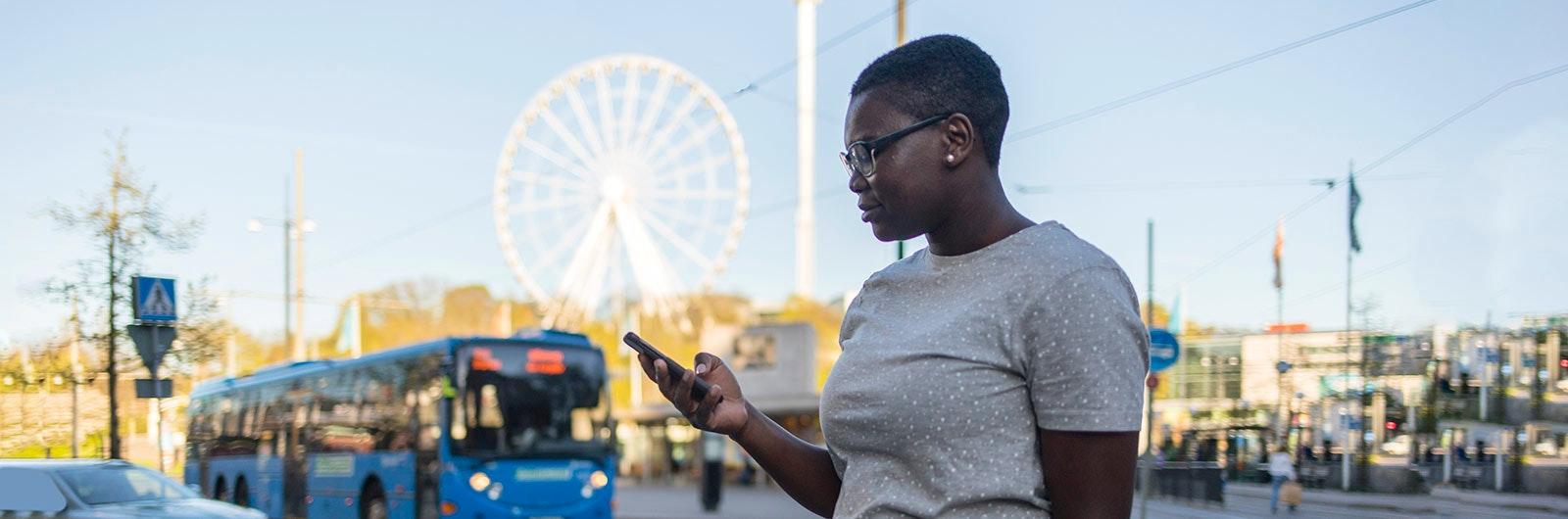 Kvinna kollar i mobil staden Göteborg