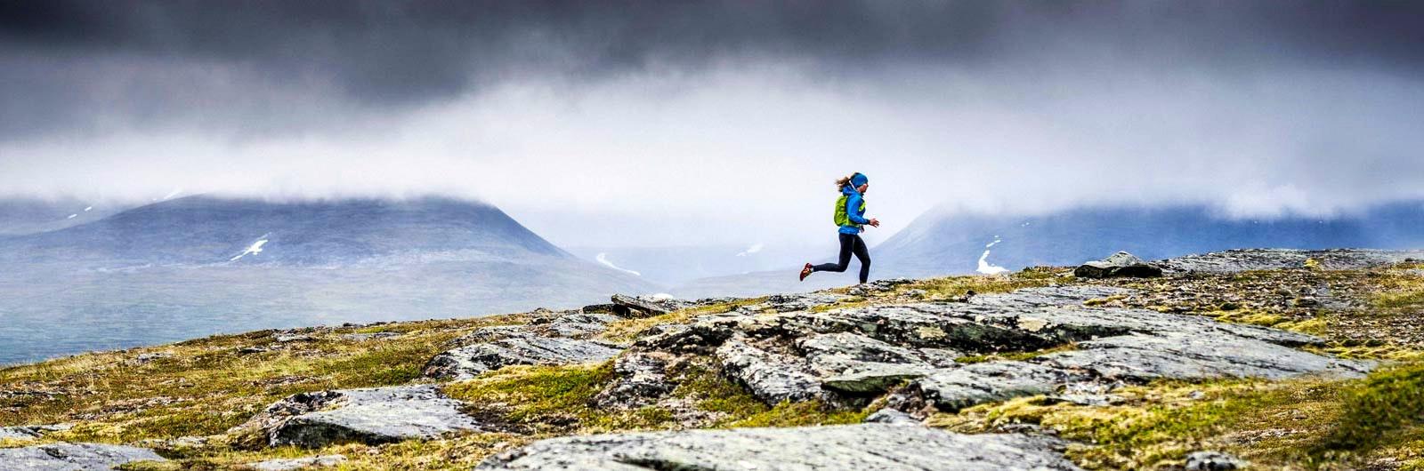Kvinna springer i fjällen på träningsresa