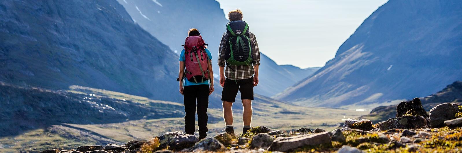 Två fjällvandrare beundrar utsikt över berg