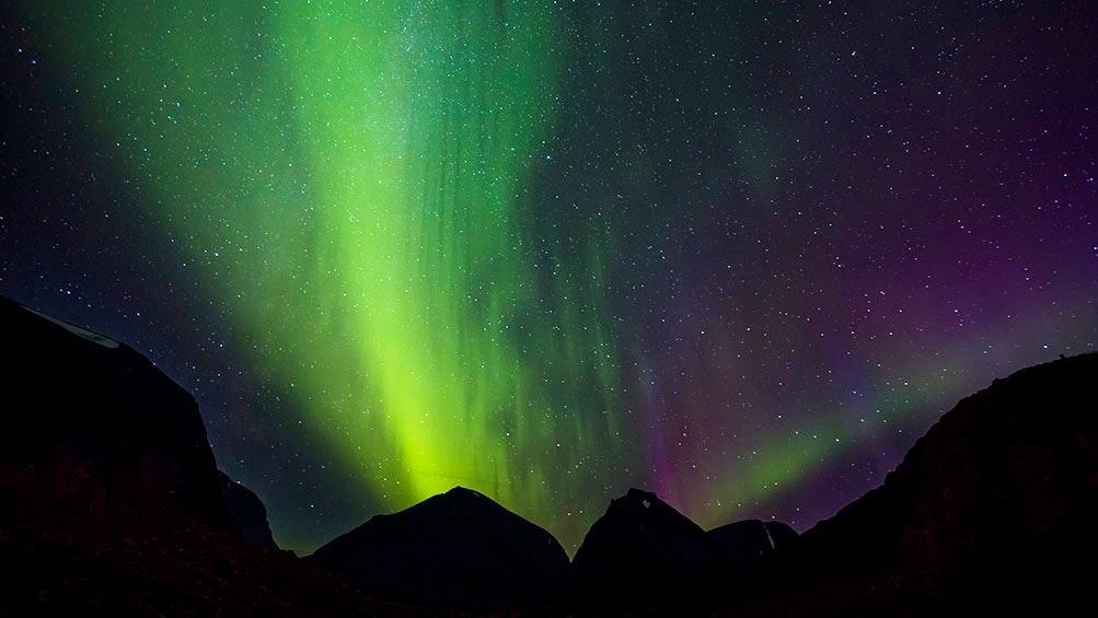 Grönt och rosa norrsken ovanför bergssilhuett
