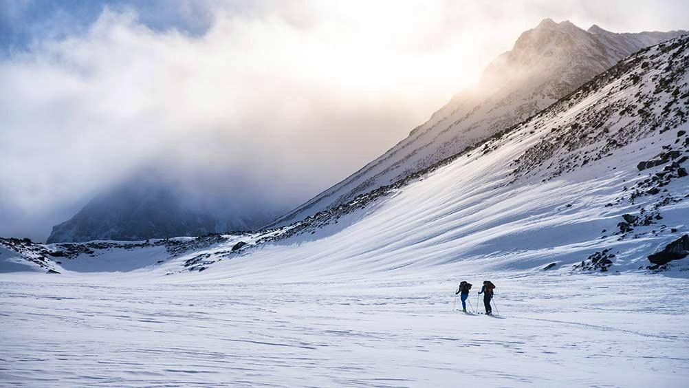 Skidåkare på avstånd intill snöklätt berg