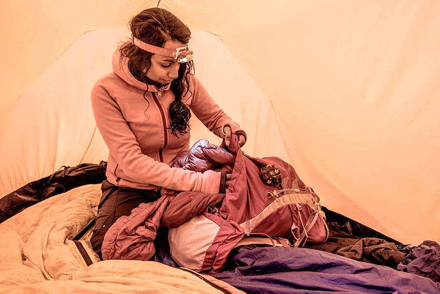 Tjej packar ryggsäck i tält