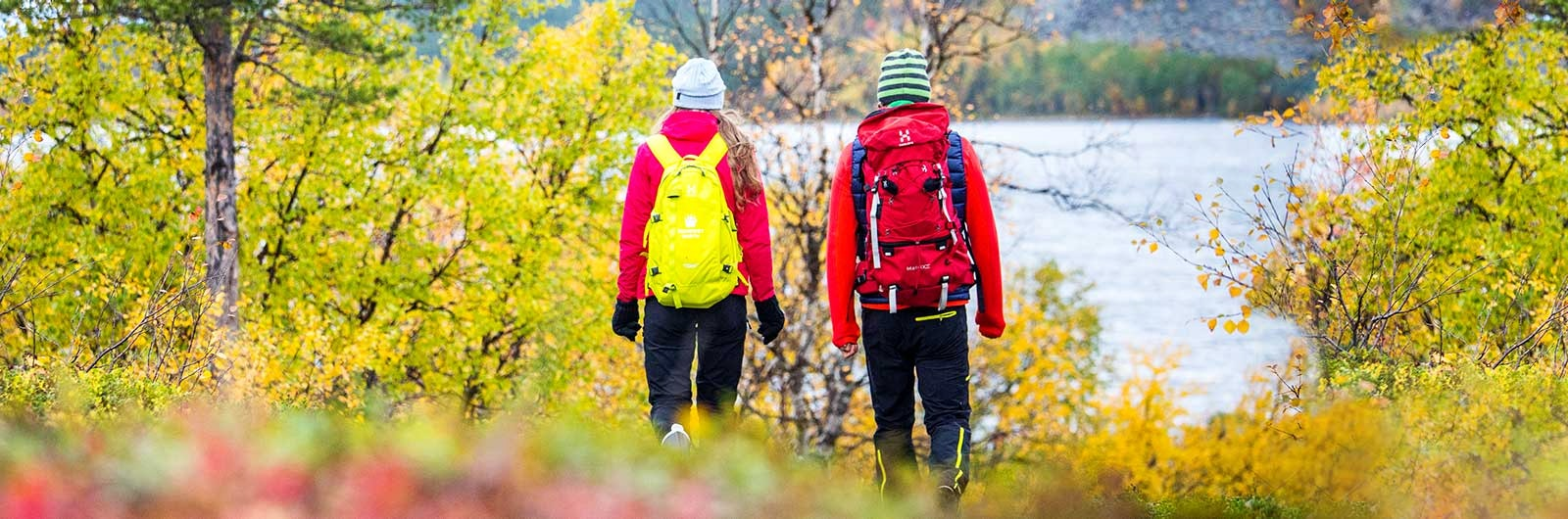 Vandrare med ryggsäckar vid sjö
