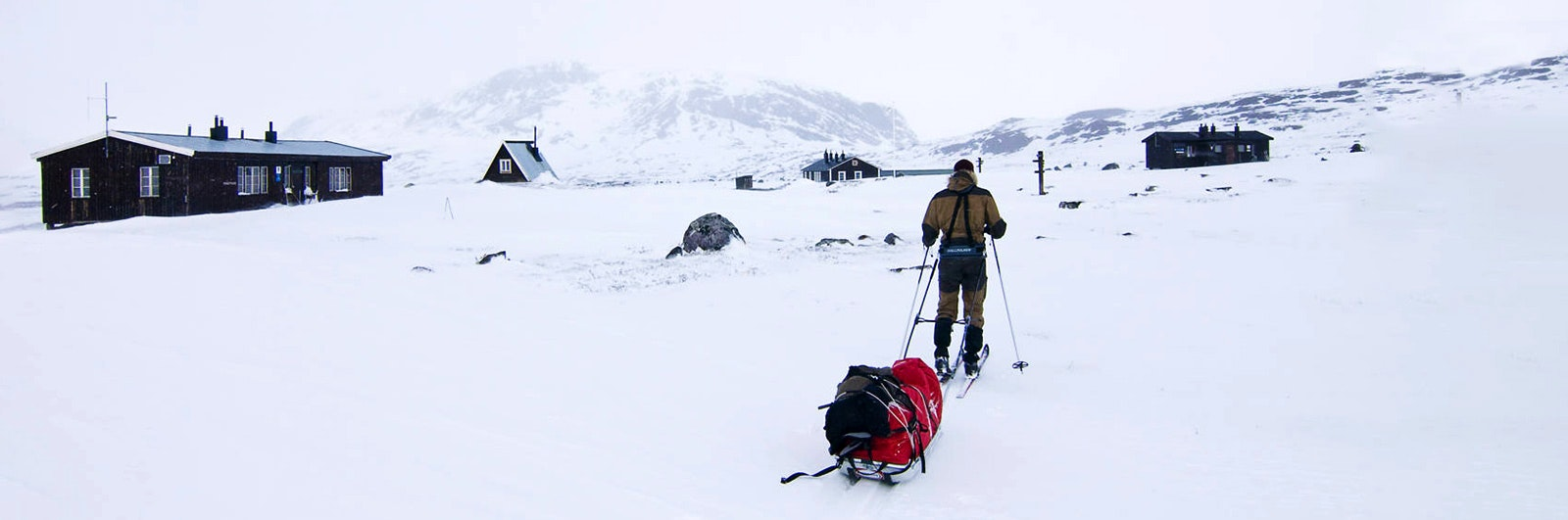 Skidåkare med pulka intill fjällstuga