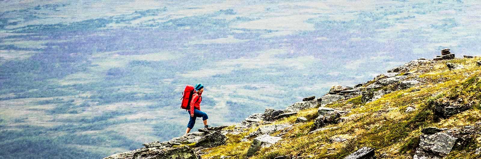 Kvinna vandrar på stupbrant berg längs Kungsleden