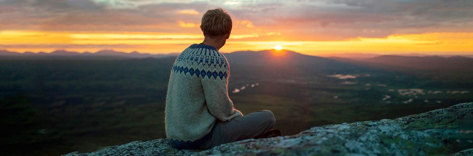 Person ser solens upp- och nedgång