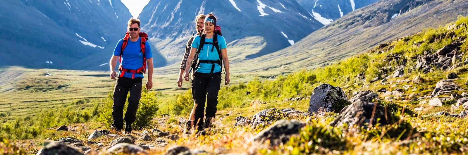 Tre vandrare i fjällmiljö på sommaren
