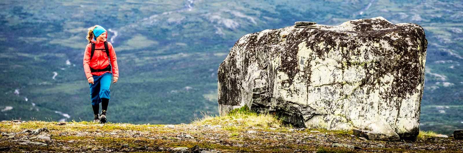Ensam vandrare vid stor sten på fjället