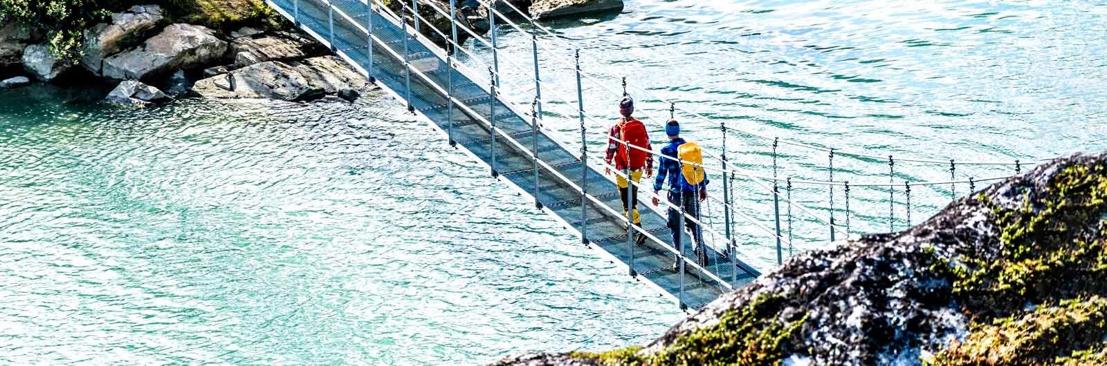 Två vandrare på hängbro i solsken