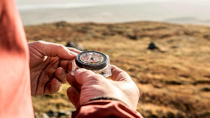 Närbild på kompass med fält i bakgrunden
