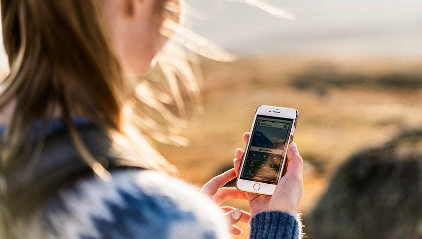 Tjej använder mobil i fjällen