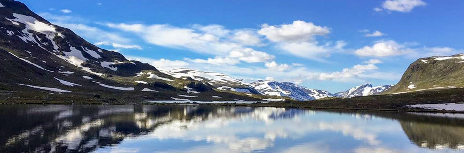 Fjäll med reflektioner i spegelblank sjö