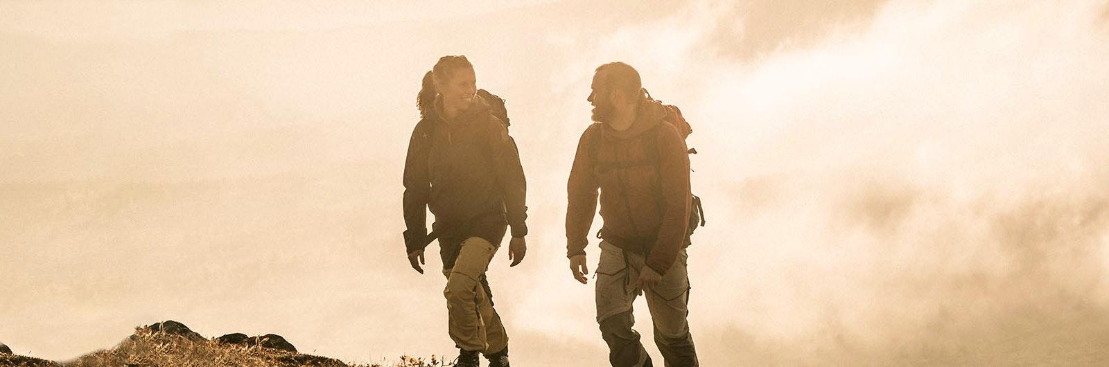 Två fjällvandrare i dimmigt motljus