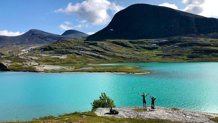 Familj som fjällvandrar intill klarblå sjö