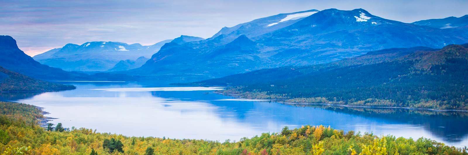Klarblå sjö mellan kantiga fjäll
