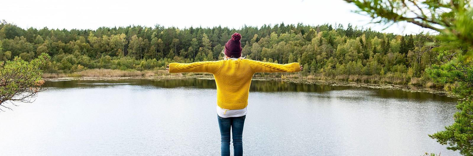 person med utsträckta armar vid sjö