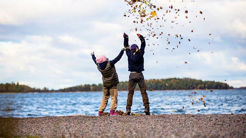Barn leker med höstlöv på svartsö i stockholms skärgård